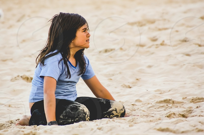 emotional preteen girl sitting on sand at the beach photo