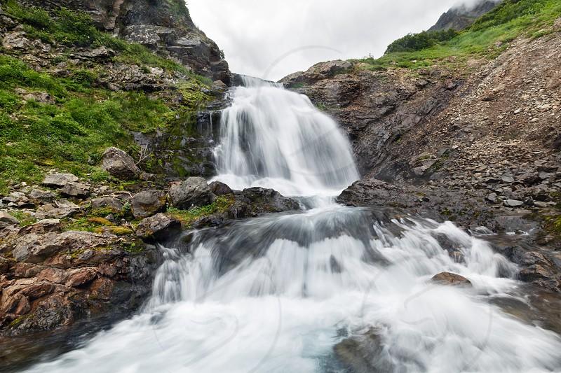 Summer mountain landscape of Kamchatka Peninsula: beautiful view of waterfall in Mountain Range Vachkazhets. Eurasia Russian Far East Kamchatka Region. photo