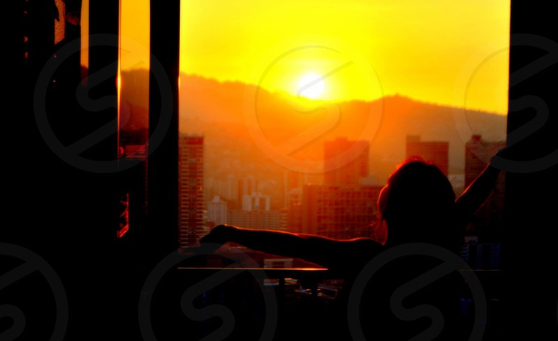 silhouette of person standing near window in golden hour background photo