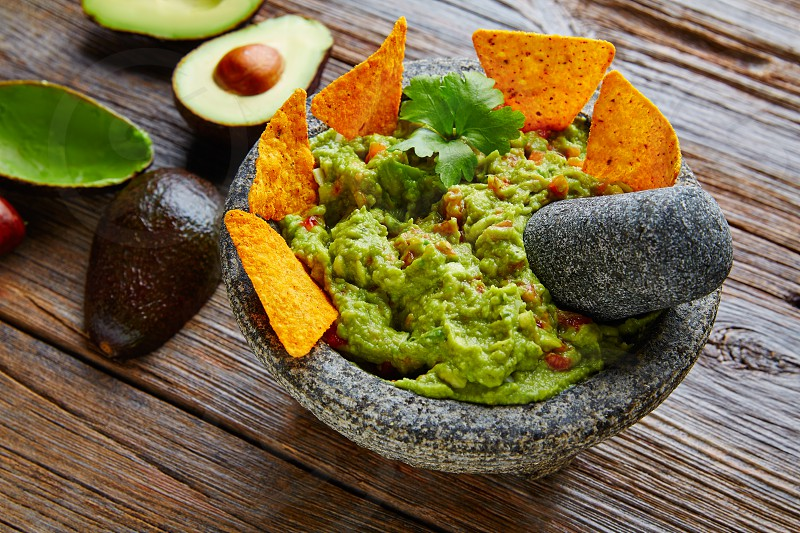 Guacamole with nachos avocado in Mexican molcajete in aged wood table photo