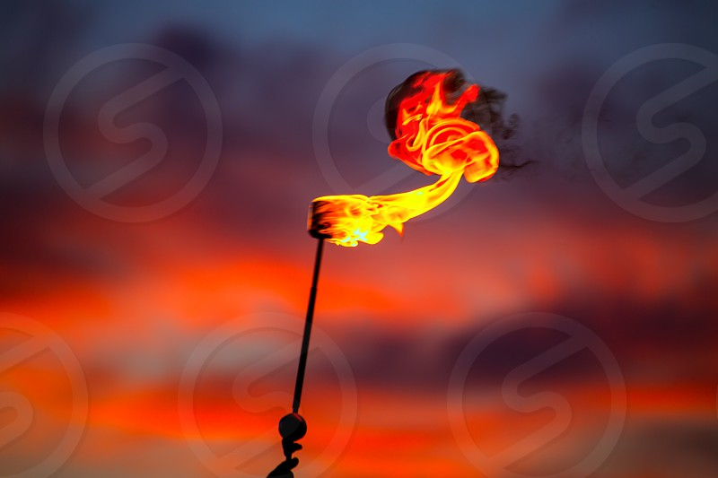 Fire torch at sunset sky with red clouds background photo