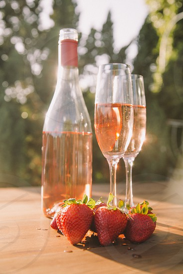 two champagne flutes filled with rose wine on a table next to the bottle and strawberries under the sun photo