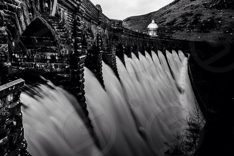 grayscale photo of water dam with bridge near mountain at daytime photo