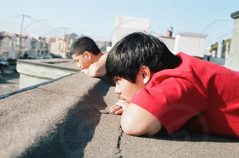 2 boys leaning on a gray concrete pavement photo