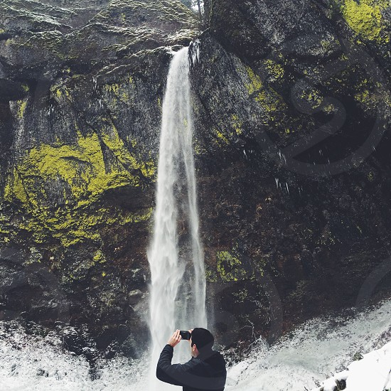 man taking a photo of a waterfall photo