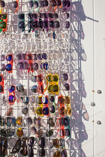 assorted sunglasses on white rack photo