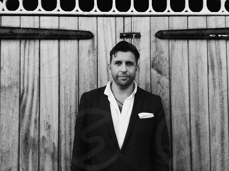 man in black blazer standing and leaning on wooden wall in grayscale photography photo