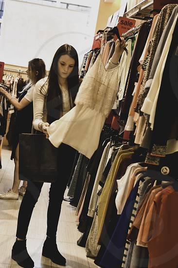 Teenage girl shopping in clothes store. photo