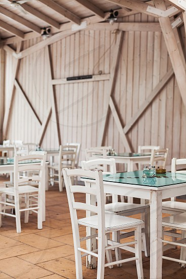 One part of wooden restaurant balcony view on chairs and tables. photo