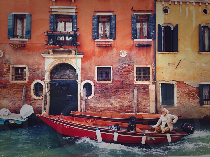 Man with dog in gondola. Black dog Venice venega gondolas gondola street street life canals canal friends friendship duo trip happy bright bright street architecture architectural building buildings Italy traveling travel white haired older character.  photo