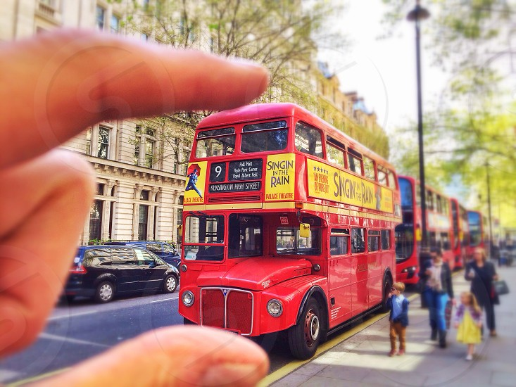 Forced perspective photo of a London Routemaster bus being grabbed by fingers.  photo