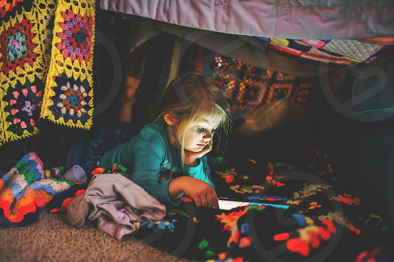 girl playing on tablet in blanket tent photo