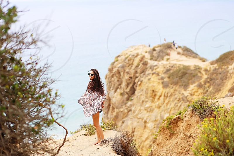 woman standing at beach shore during daytime photo