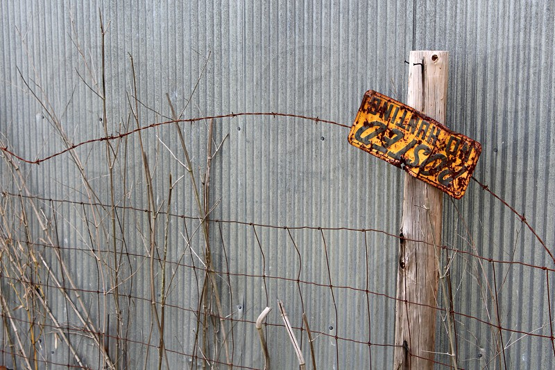 Old barbed wire fence against tin wall with Posted No Hunting sign yellow and rusted photo