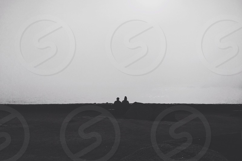 two people sitting on sand photograph  photo