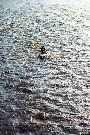 People kayaking on the Dunajec river. Two young adults sitting in a kayak and they paddling together down the river. Couple enjoying ride surrounded by small waves photo