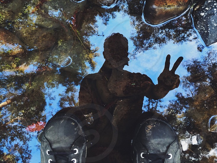 reflection of man making peace sign on water puddle photo