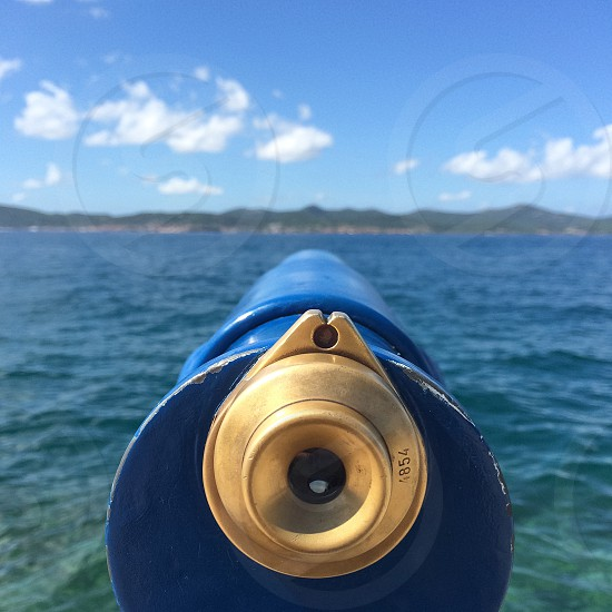 brass 4854 round accessory on blue cylindrical pipe near blue seawater below white clouds and bright blue sky during daytime photo
