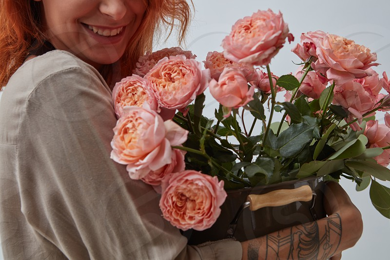 Happy woman with a tattoo on her hand holds a vase with beautiful pink roses. Mothers Day. photo