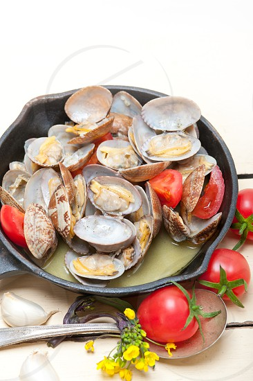 fresh clams stewed on an iron skillet over wite rustic wood table  photo