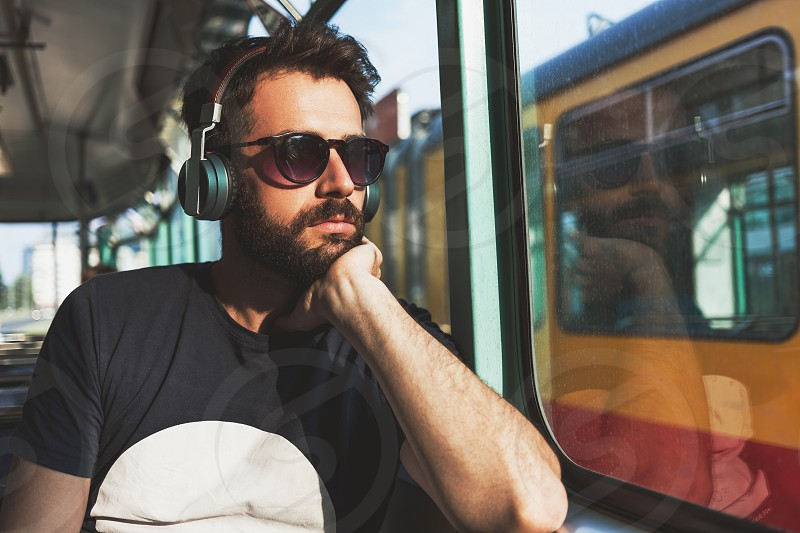 Young man riding in public transport listening to the music photo