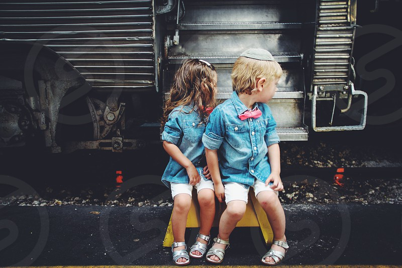 boy and girl in matching denim and sandals looking at train behind them photo