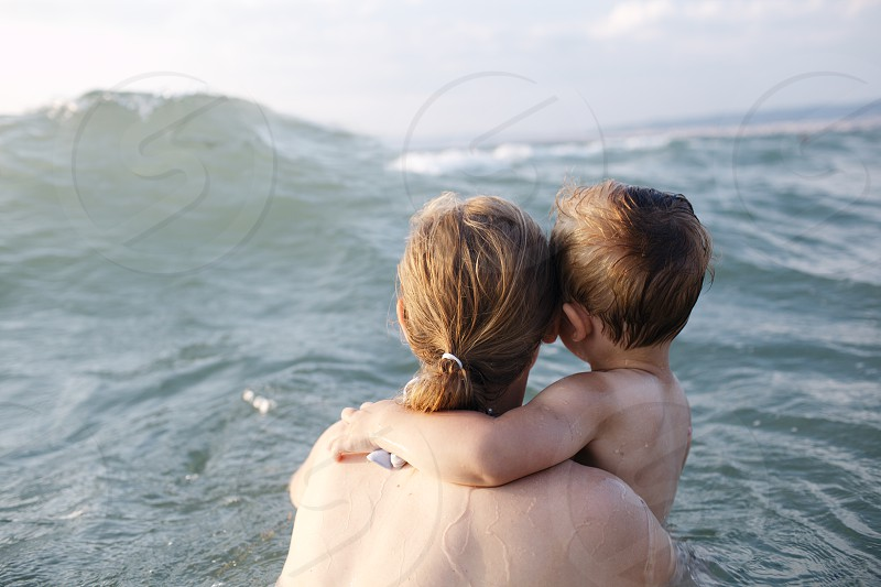 Mother swimming in the sea with her small son in her arms watching an oncoming wave view from behind them photo