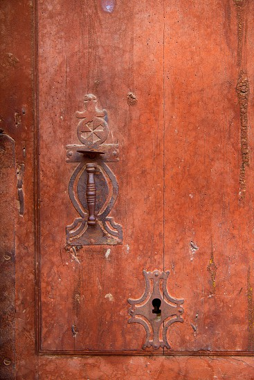 Aged old vintage door knob and keyhole in weathered grunge red wood photo