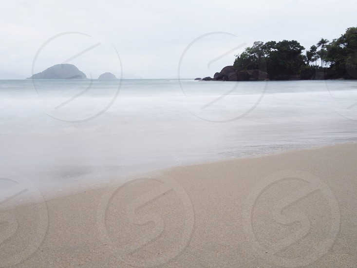 white water on beach under gray cloudy sky photo