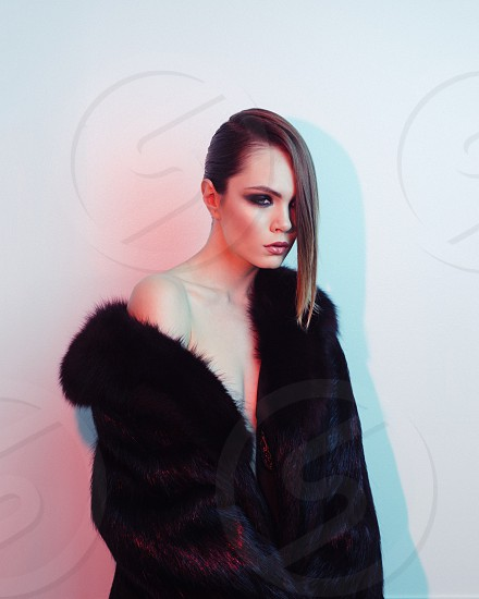 woman wearing black mascara and black fur coat against white wall photo