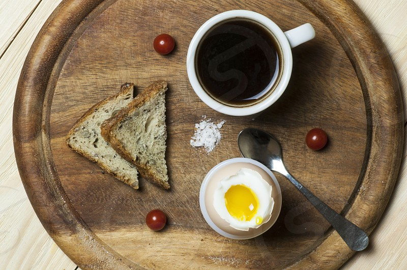 light breakfast of boiled egg piece of toast cup of coffee and cherry tomatoes on cutting board view from above photo