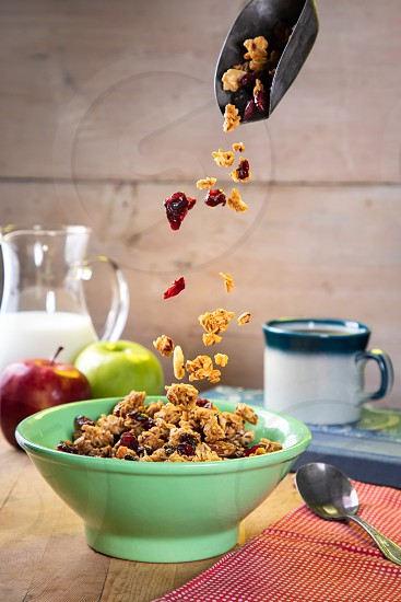 Breakfast Granola and Cranberries being poured into a green bowl photo