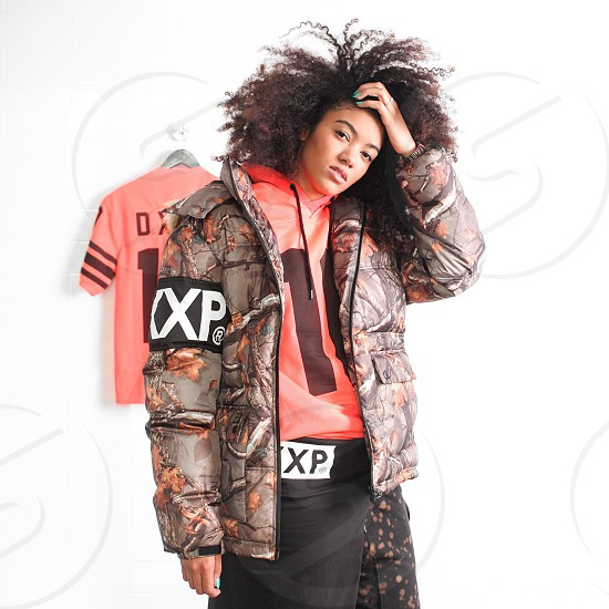 man wearing a puff jacket ad red hoodie and black pants photo