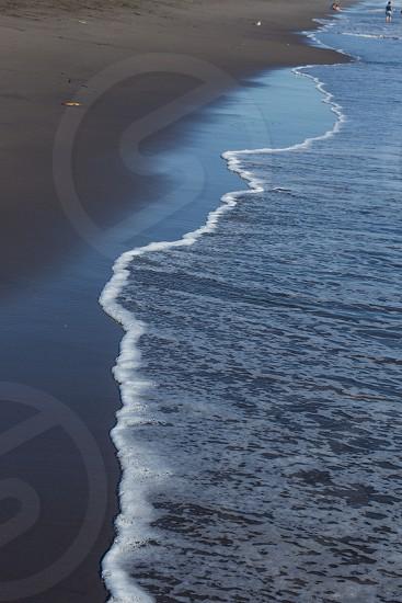 Incoming tide Pacific Ocean beach dark sand photo