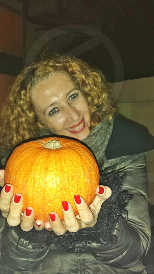 woman in gray bubble jacket holding orange pumpkin while smiling photo