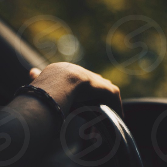 person wearing bracelet holding steering wheel photo