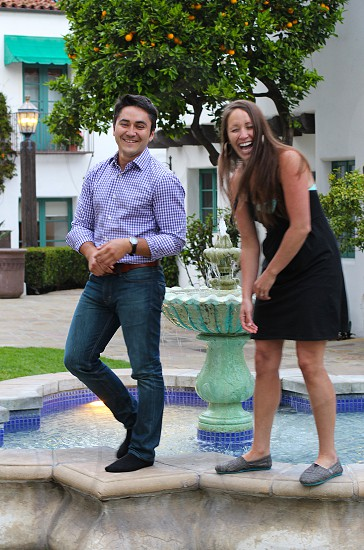 Young man and woman laughing next to fountain.   photo