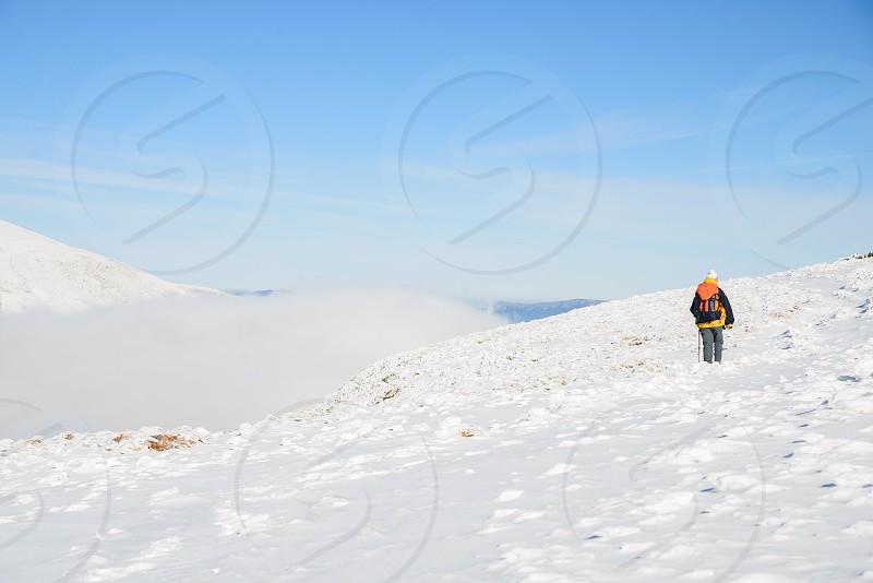 Tourist climbs the snow-covered mountain photo