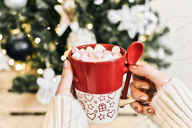 Woman's hands holding a red mug. Hot beverage cocoa tea coffee marshmallows christmas vibe. photo