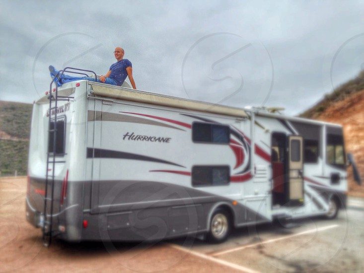RV Road Trip with passenger chilling on roof whilst parked.  photo