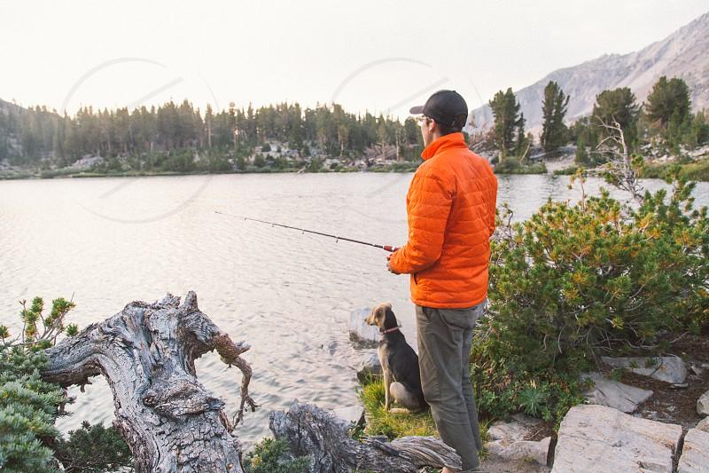 man holding casting rod fishing on calm body of water next to black short coat medium size dog during daytime photo