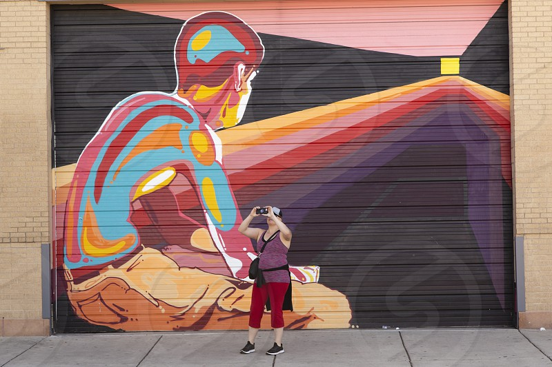 Woman with obscured face photographing street scene with mural in background Denver Colorado photo