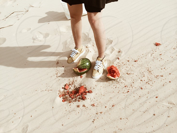 crushed green watermelon on brown sand photo