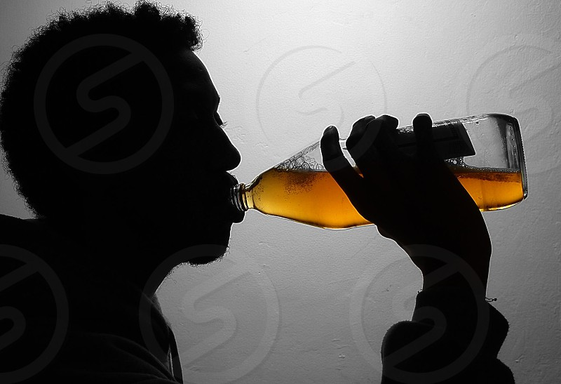 silhouette photography of man drinking glass bottle filled with brown liquid photo