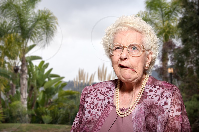 An elderly woman in a lush yard is wearing a formal dress and pearl necklace as she makes a funny face. photo