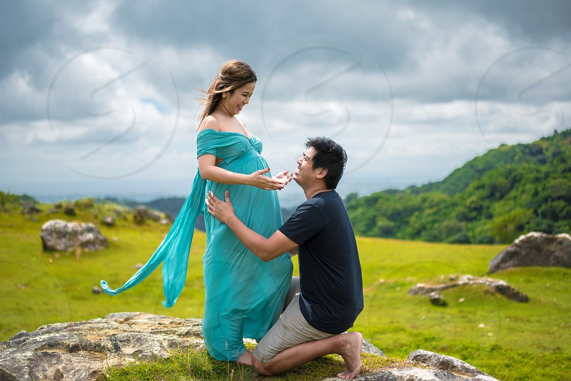 man kneeling in front of woman surrounded by green grass during daytime photo