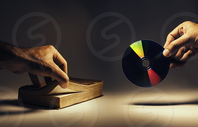 Conceptual composition about archiving data old way as a book and new as a CD.  photo