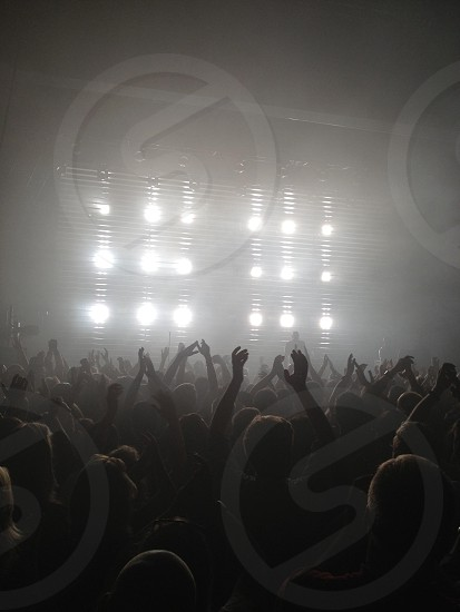 people raising hand in front of stage photo