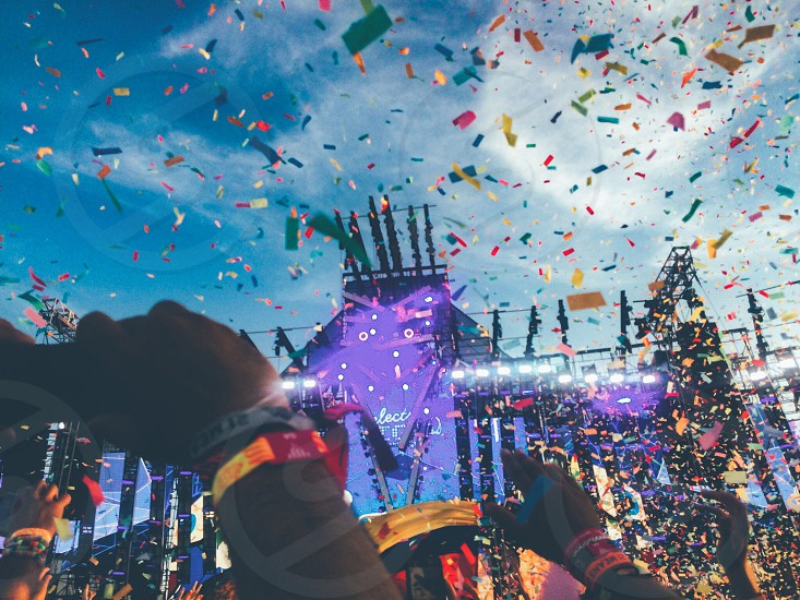 people partying wearing orange and blue wristbands with confetti falling from the sky during daytime with cirrus cloud formation photo