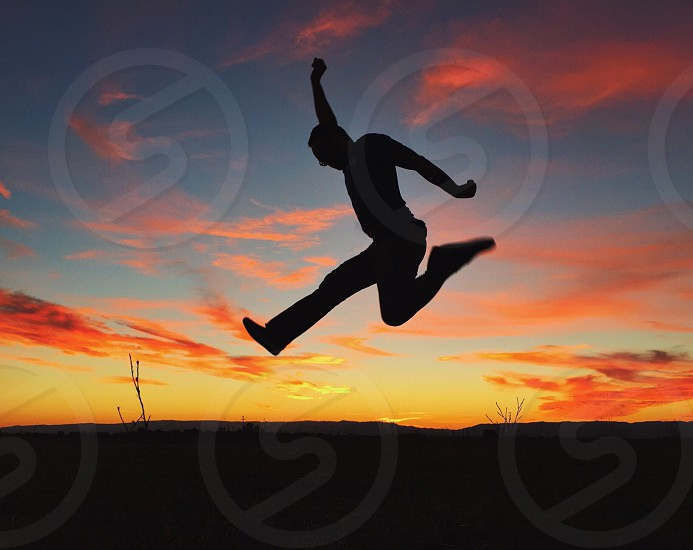 man silhouette jumping photo